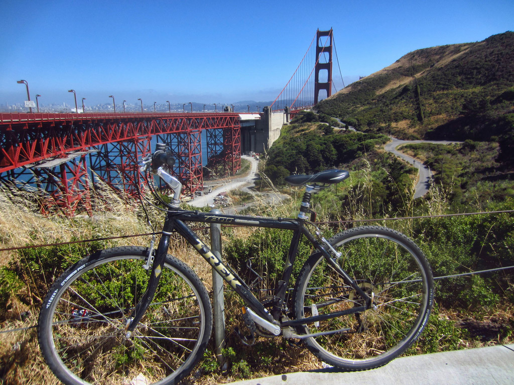 Bike resting along a path with the Golden Gate Bridge in the background.