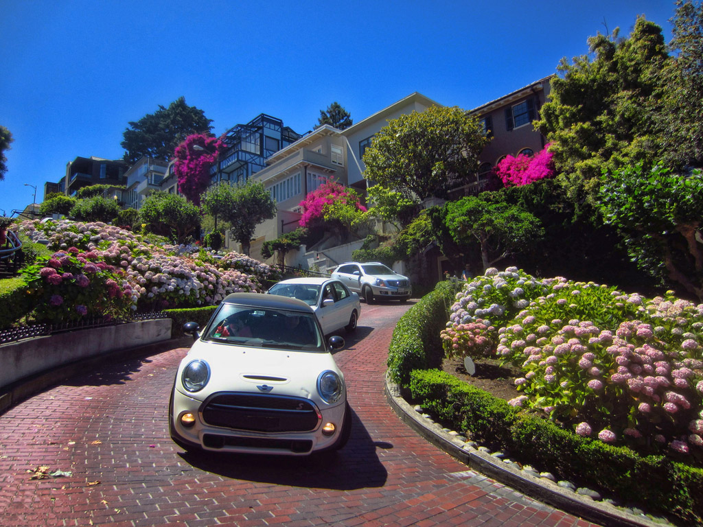 Cars winding down cobblestone street with beautiful landscape on either side of the road and houses towering above..