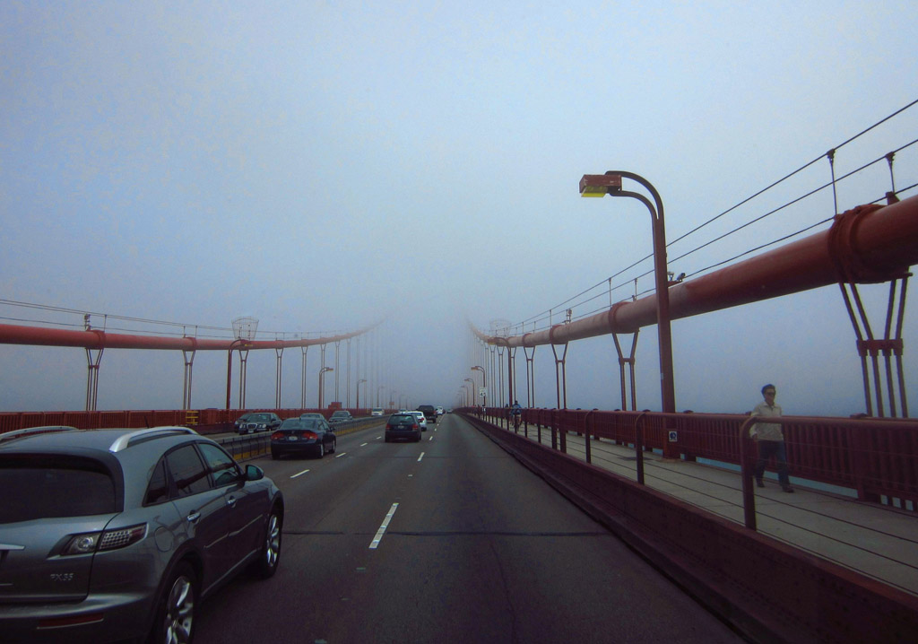 Cars crossing the Golden Gate Bridge heading into a thick fog.