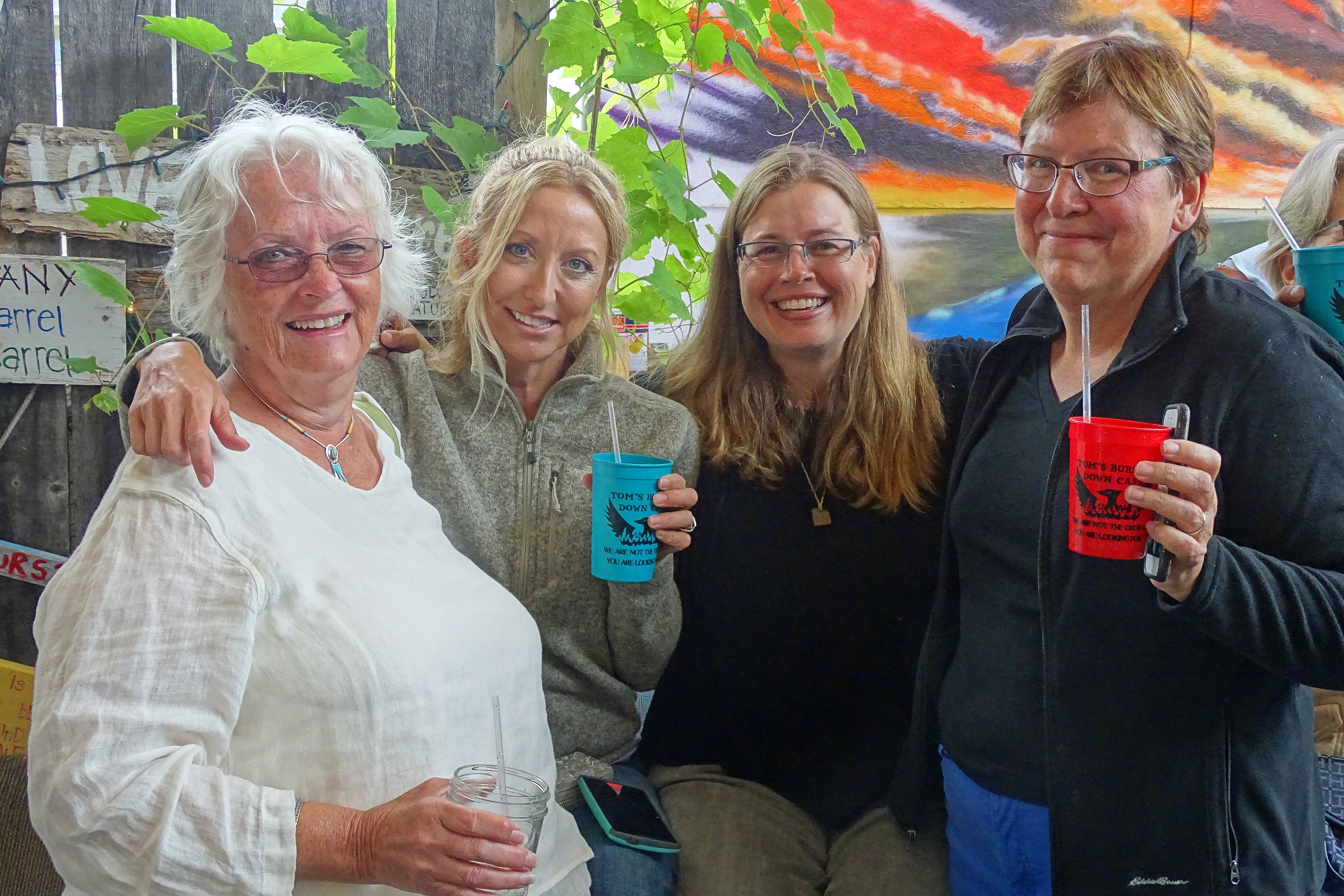 Four ladies smiling and two holding drinks.