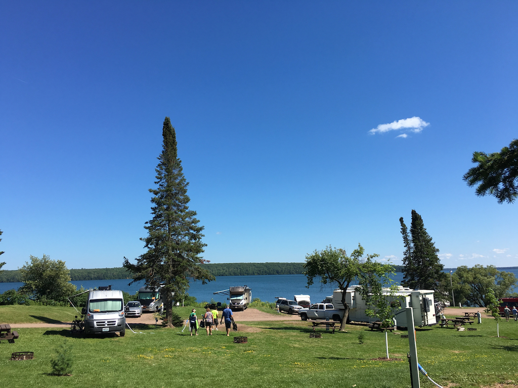 RVs parked at campground along the water with clear blue skies above.