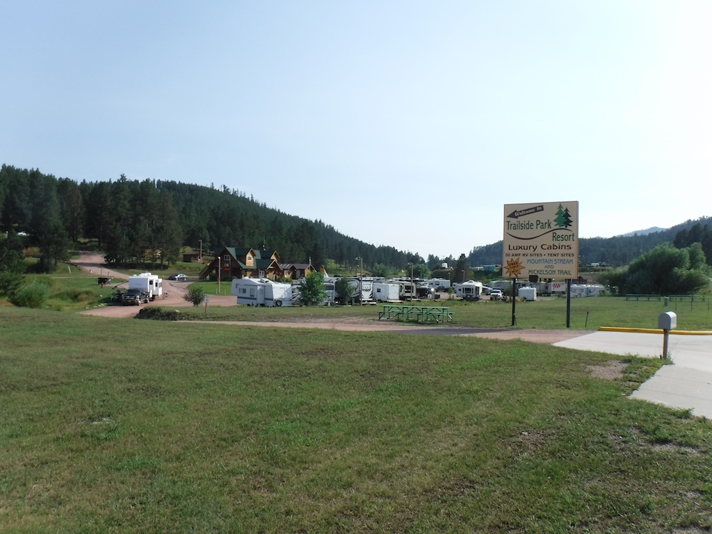Trailside Park Resort nestled against tree covered hills with RVs parked throughout