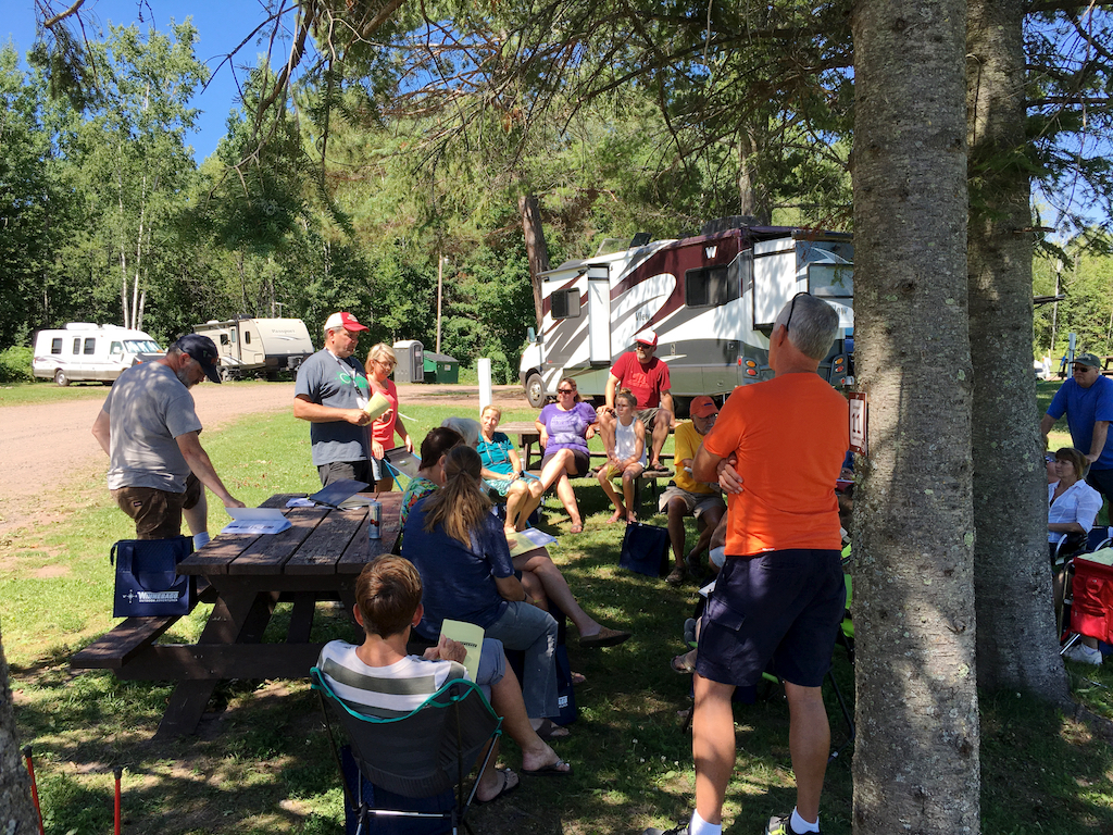 Group gathered around a picnic table at a campground listening to someone speak.