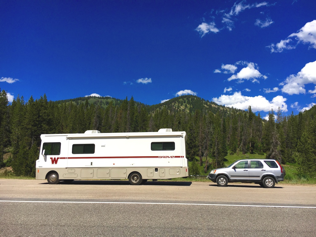 Winnebago Brave with tow car attached and parked on the side of the road with tree covered hills in the background.