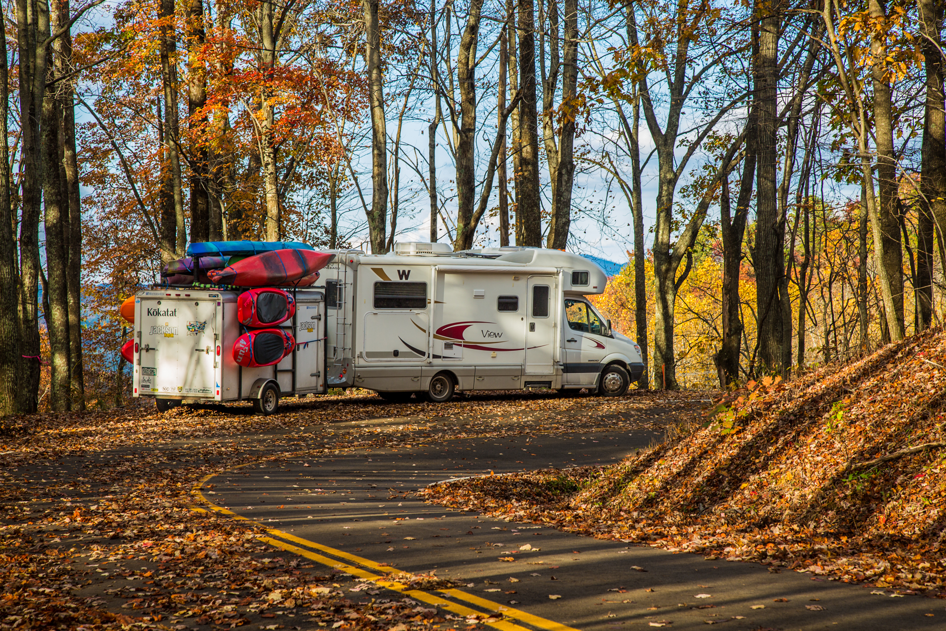 Winnebago View with trailer attached parked along the side of the road among fallen leaves.