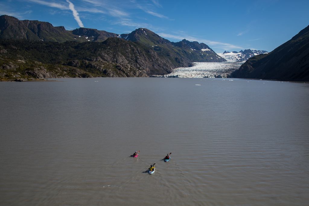Three kayakers out on glacier lake with glacier ahead.