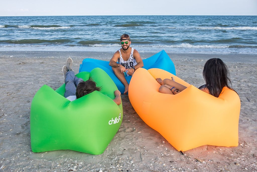 Inflatable lounge chairs in use, three young individuals lounging on the beach