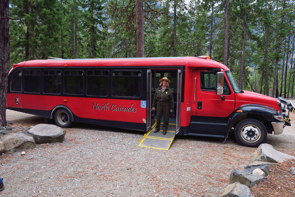 Park Ranger at the side of a red North Cascades tour bus.