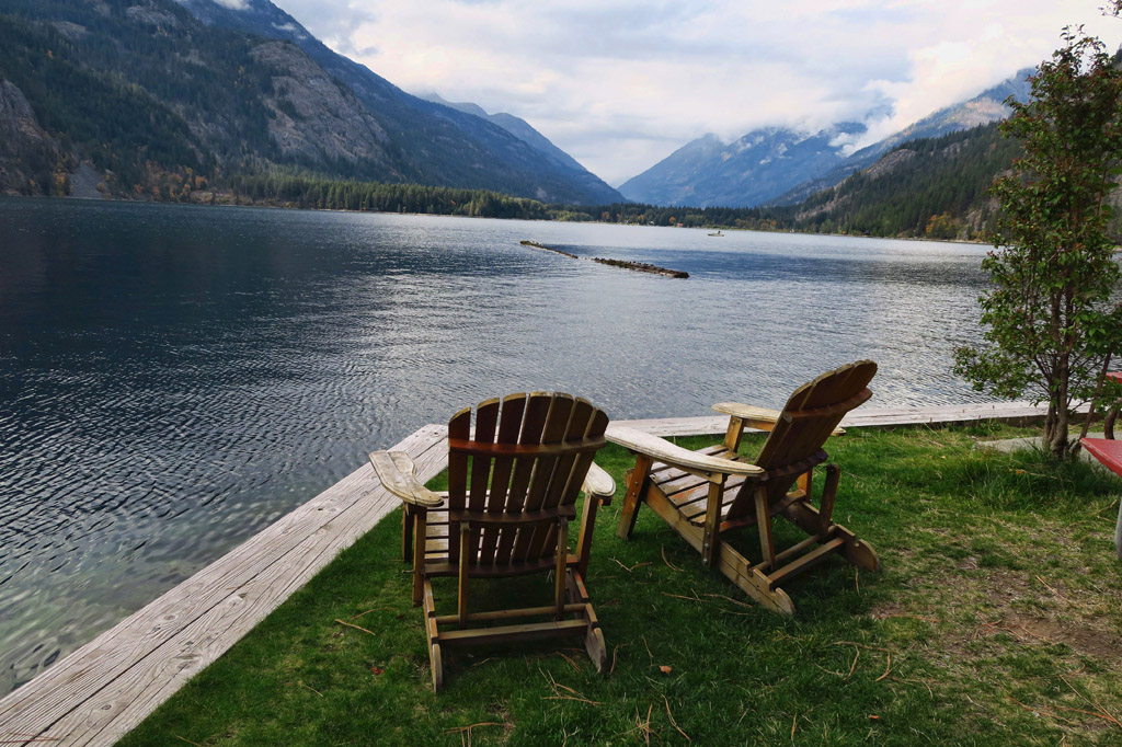 Two chairs at the waters edge with mountains surrounding the water.
