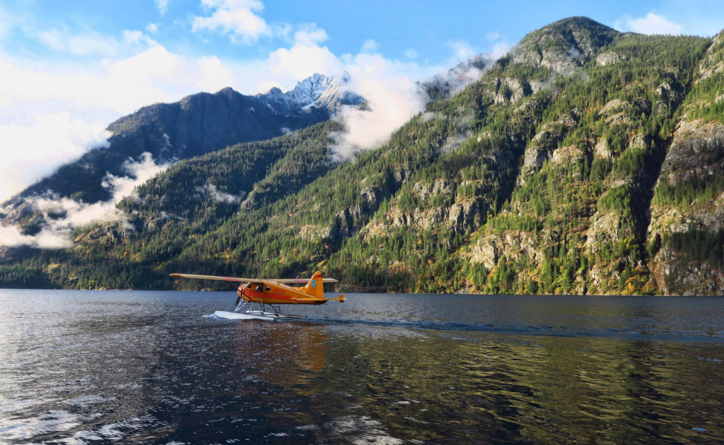 Small plane preparing to take off from the water with mountains lining the shoreline.