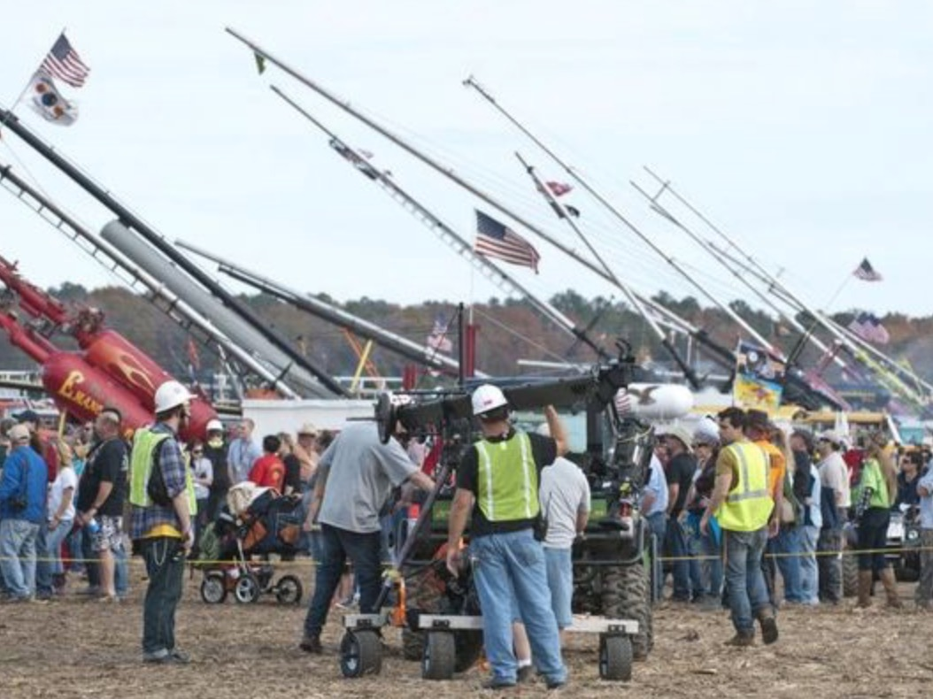 Line of punkin chunkin machines in a line with crowds gathered.