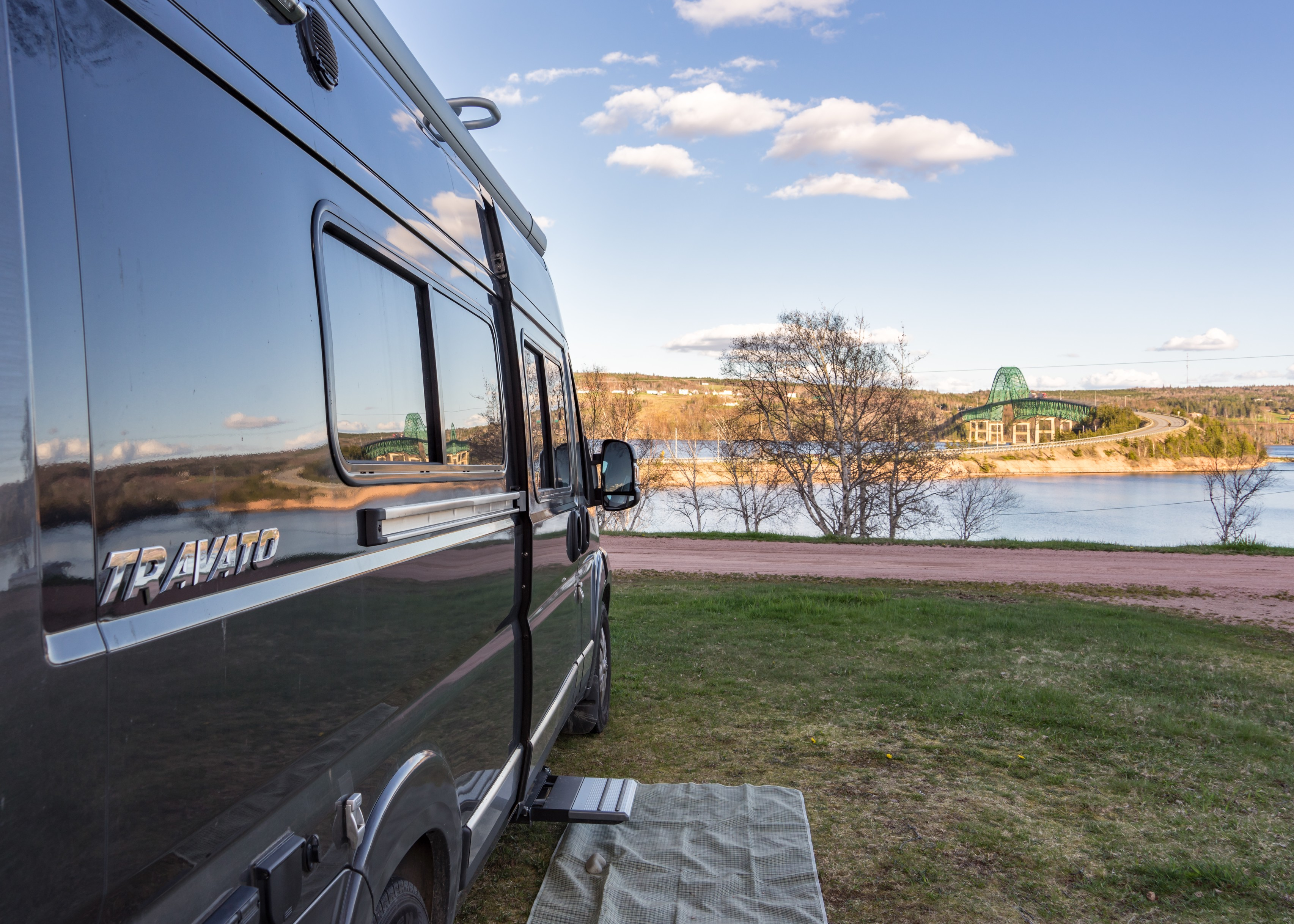 Winnebago Travato parked on the grass looking out at water ahead.