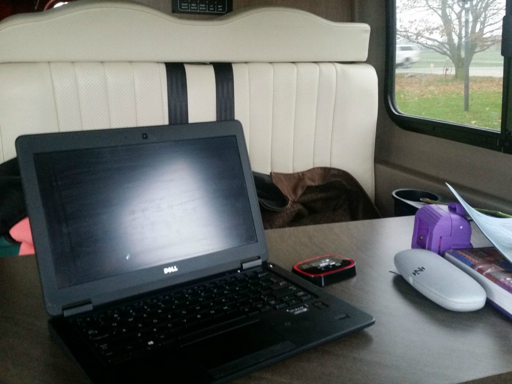 Computer among other things on the dinette of the Winnebago Travato.