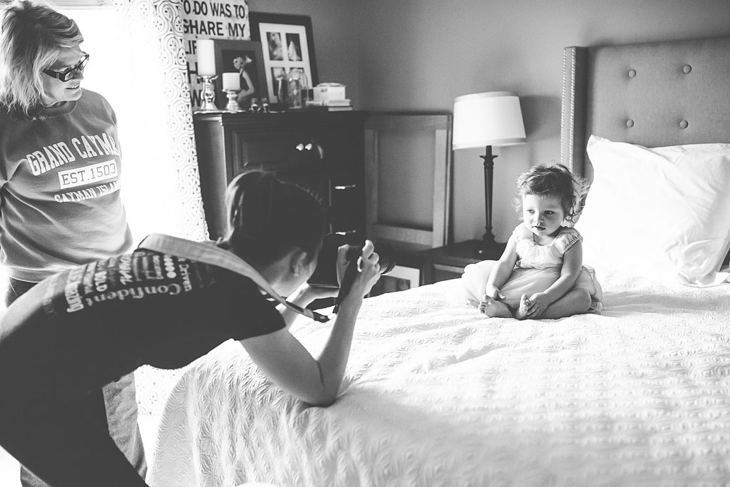 Woman taking a photo of young child sitting on a bed.