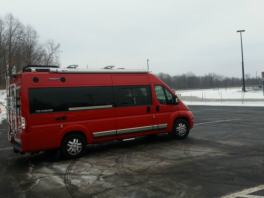 Red Winnebago Travato in parking lot with snow covering the surrounding ground.