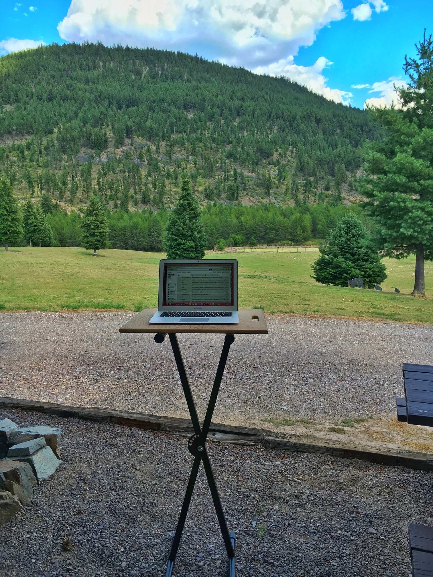 Computer at makeshift standing desk outside motorhome with beautiful tree filled hillside ahead.