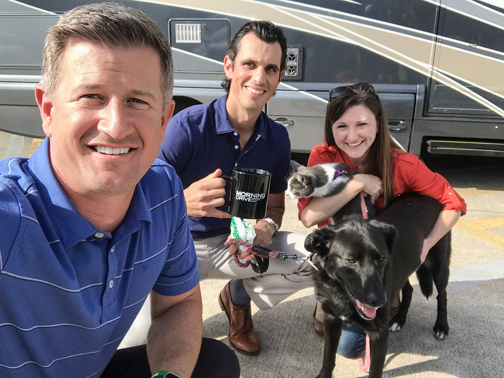Jordan, Brittany and their dog and cat with Matt Ginella taking a selfie in front of their Winnebago View.