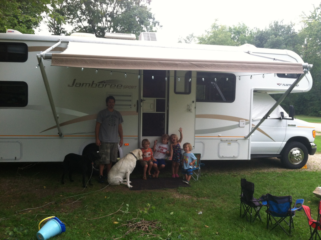 Man, 4 kids, and two dogs outside an RV.