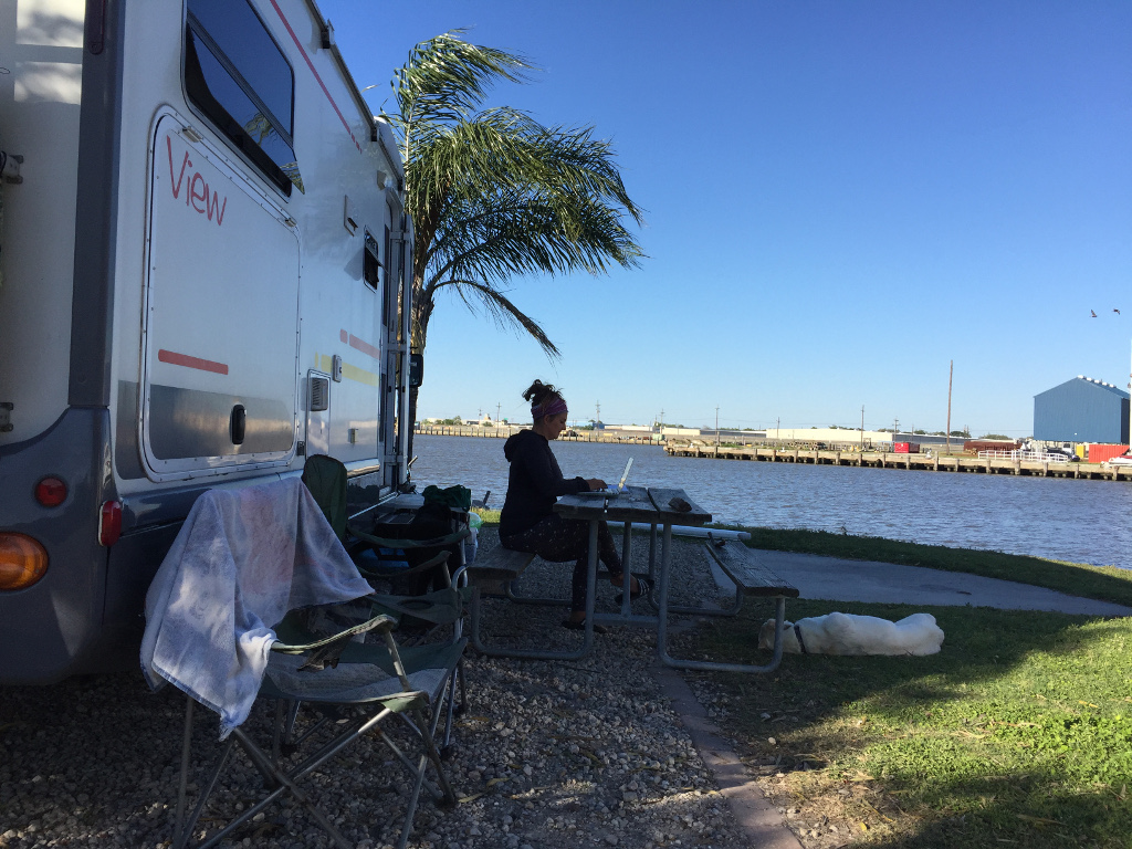 Woman working on laptop at picnic table outside RV next to the water.