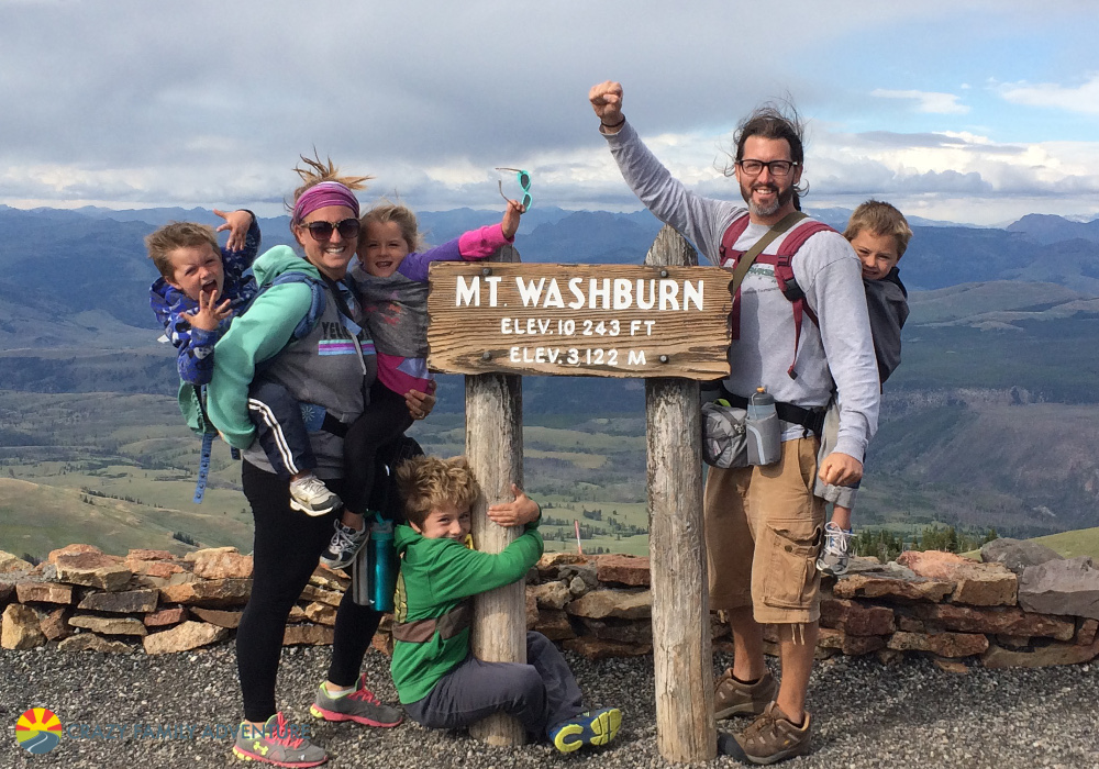 Family of 6 next to sign for Mt. Washburn with mountains in the distance.
