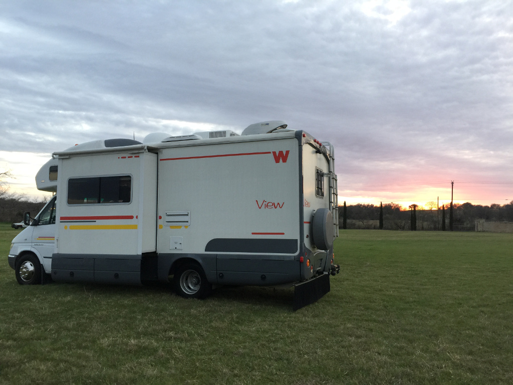 Winnebago View parked in grassy field with sun setting over the horizon.