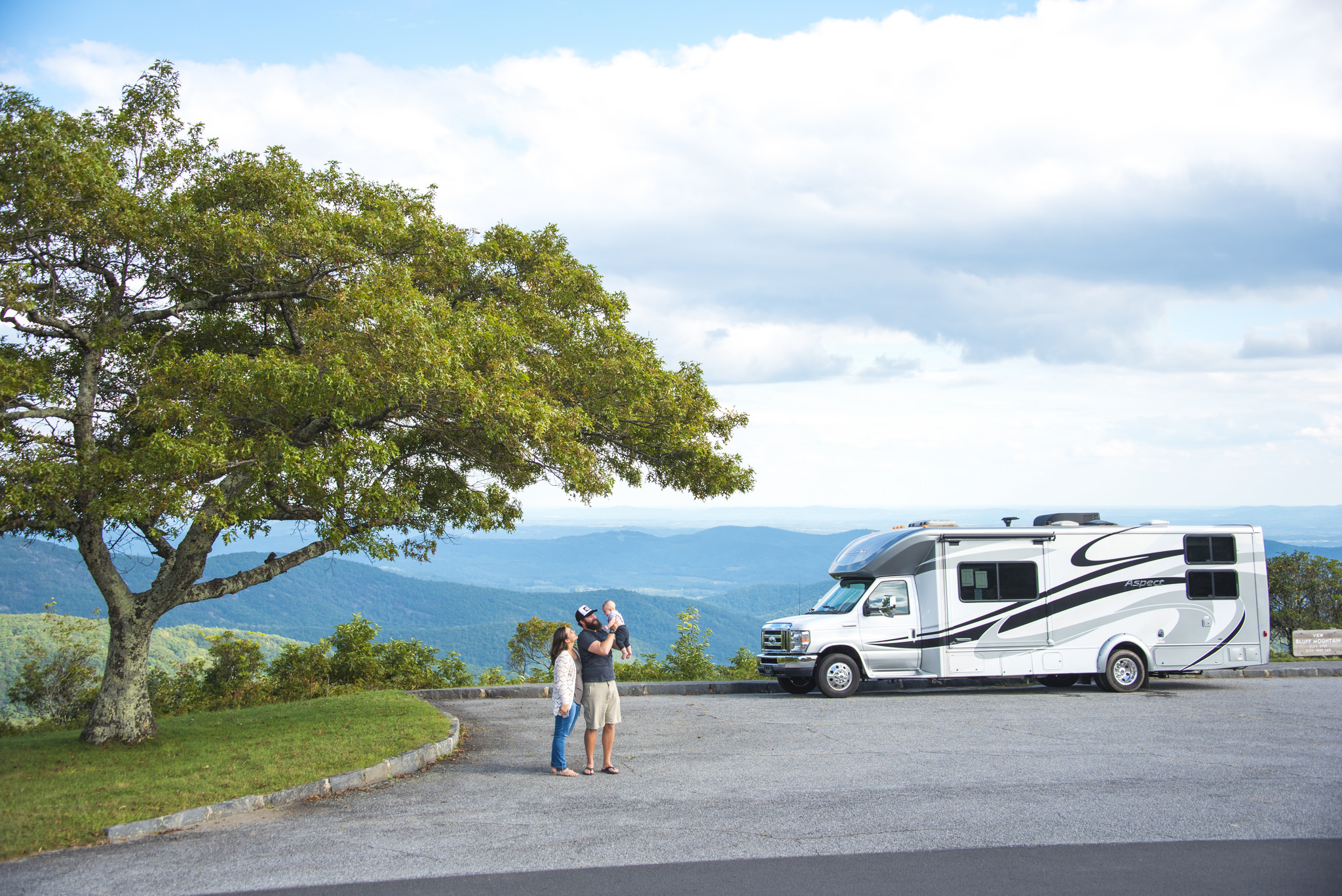 Couple with baby standing in front of their Winnebago Aspect with beautiful scenery around them.