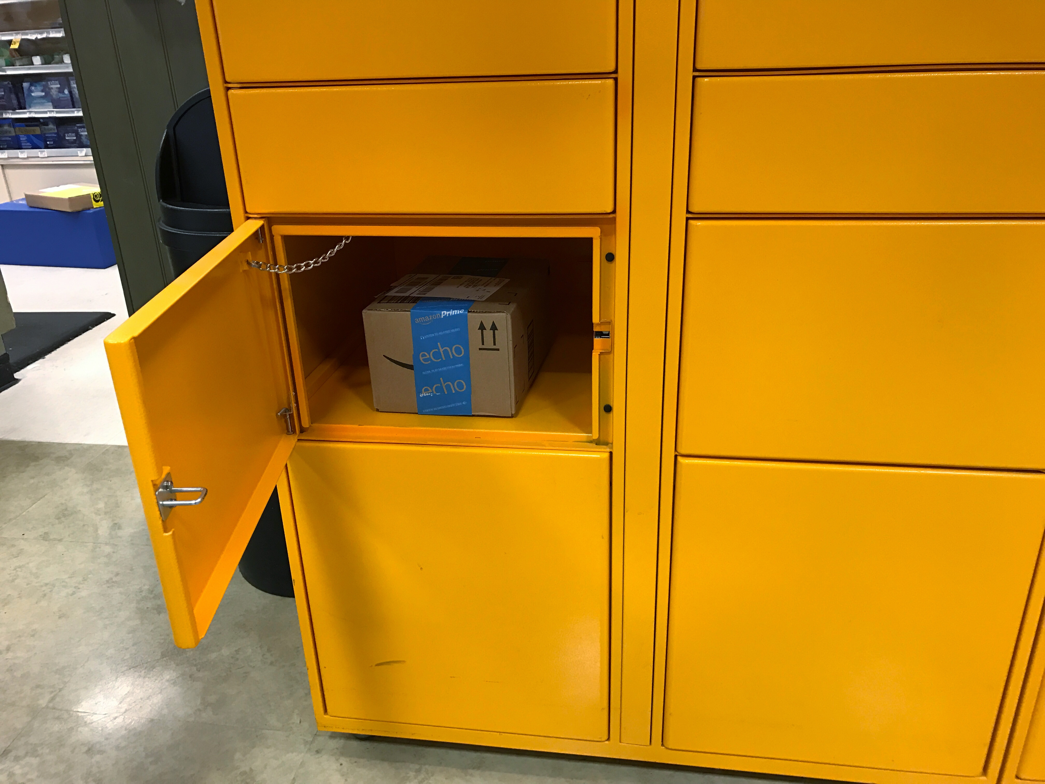 Detail view of opened Amazon locker with package inside the compartment