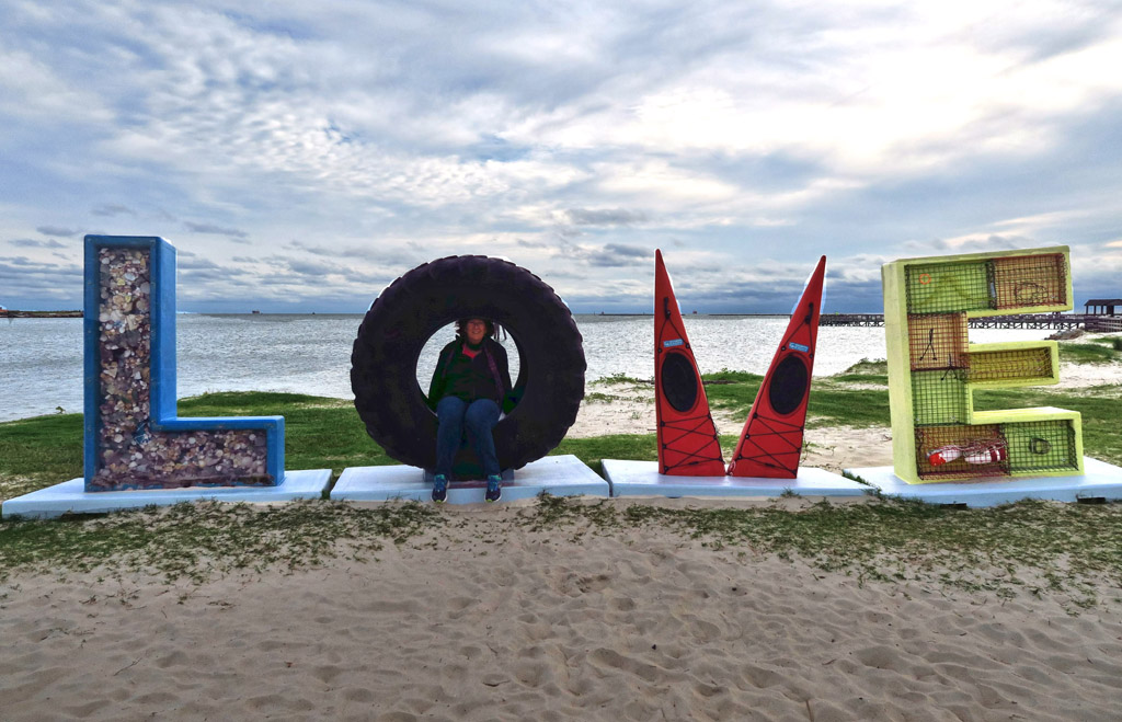 "Woman sitting in a large tire used as the ""O"" in the word ""LOVE"" spelled out on the beach with different items."