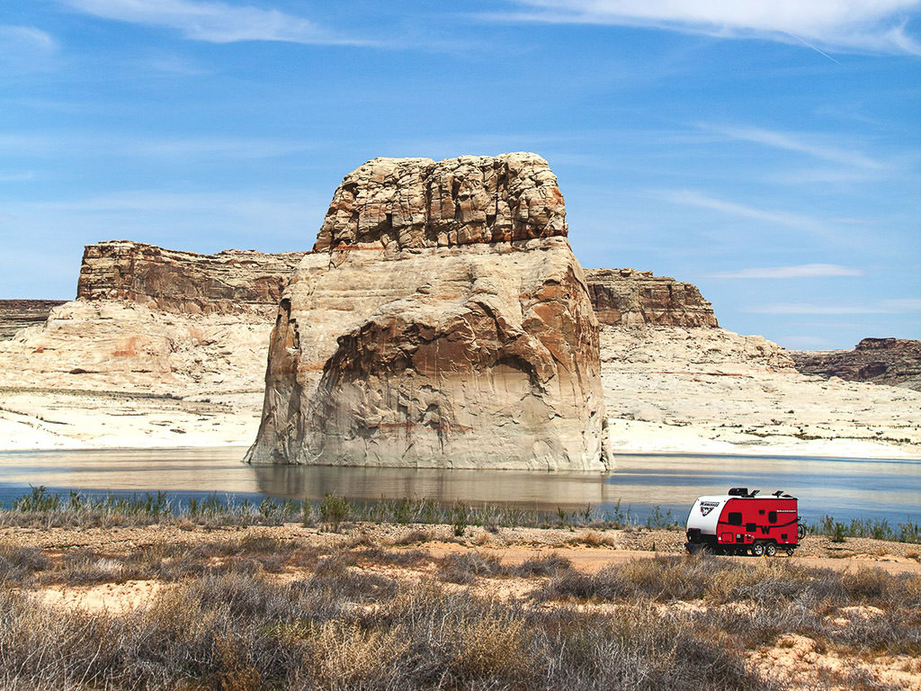 Winnebago Towable parked along the water with large, unique rock formations off shore.
