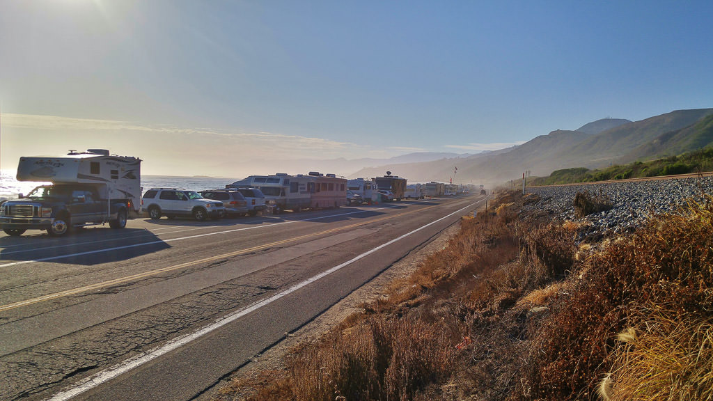 Cars and RVs lining roadway along coastline.