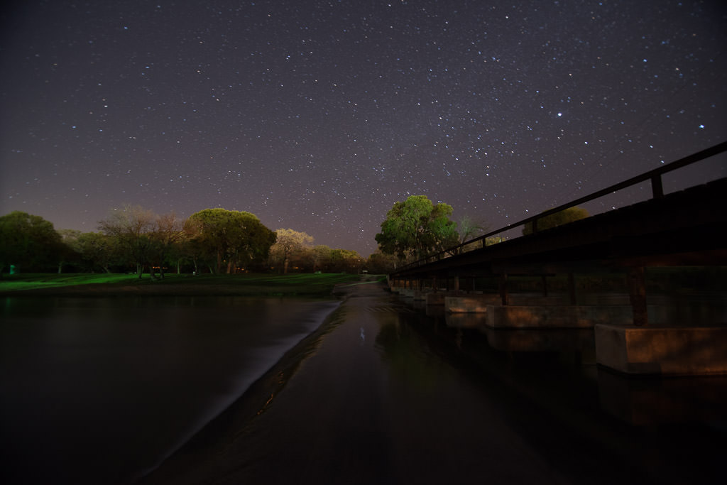 Star-filled night sky above a bridge.