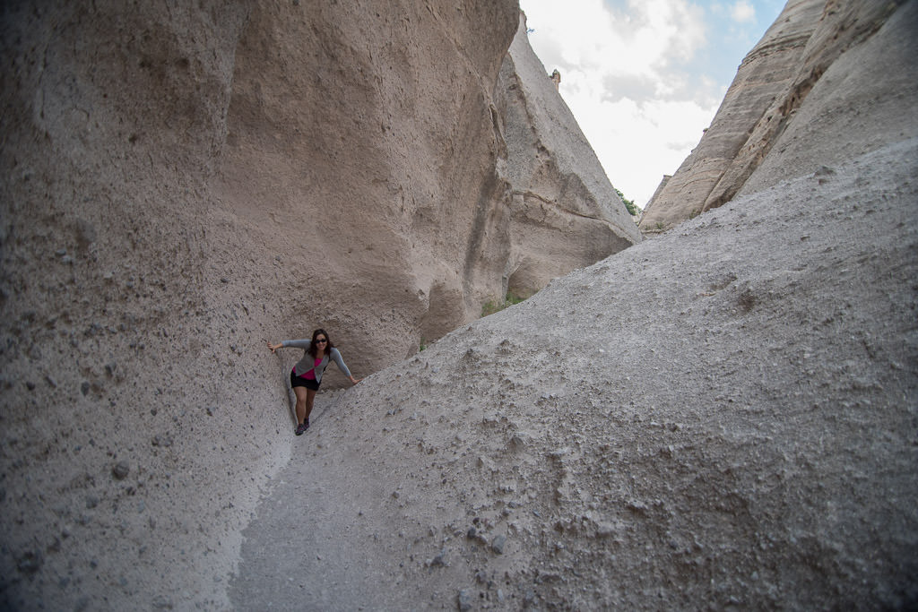 Woman climbing between narrow valley created by large rock formations.