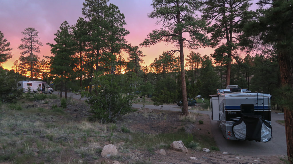 Winnebago View in campsite with colorful sunset lighting up the sky.