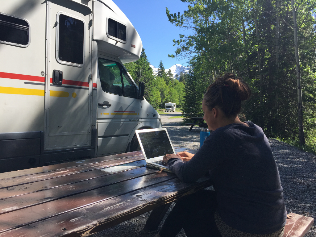 Woman on a computer at a picnic table outside her Winnebago View parked at campsite nestled in the trees and mountains peeking above the trees in the distance.
