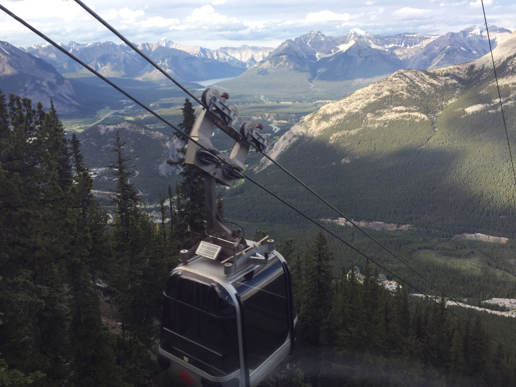 Banff Gondola overlooking breath-taking mountain range with trees and rivers running below.
