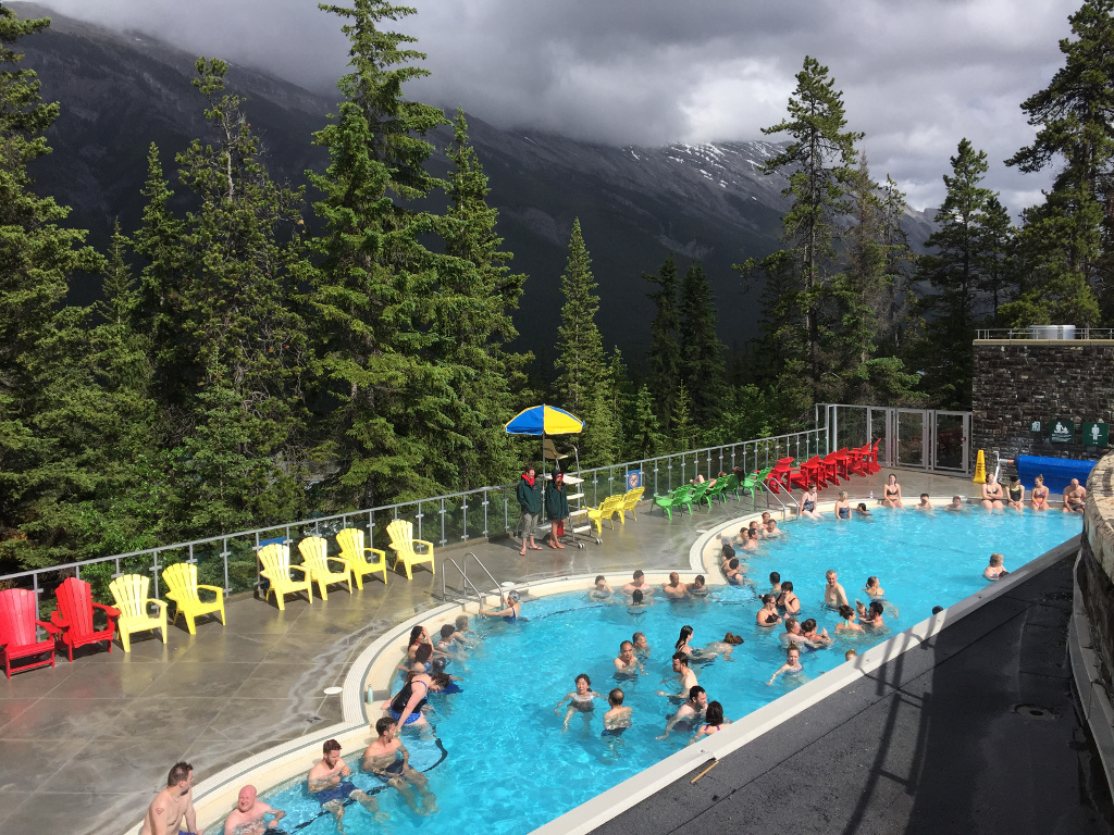 Pool  that is Banff Hot Springs on a deck overlooking the mountains.