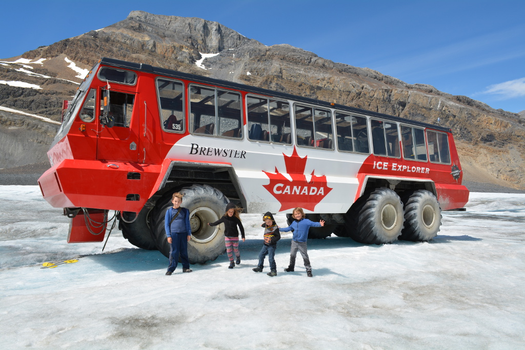 Four kids standing on the glacier outside the Brewster Ice Explorer Truck.