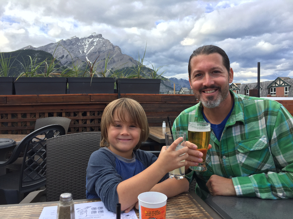 Man and child tapping drinks together on rooftop restaurant in downtown Banff.