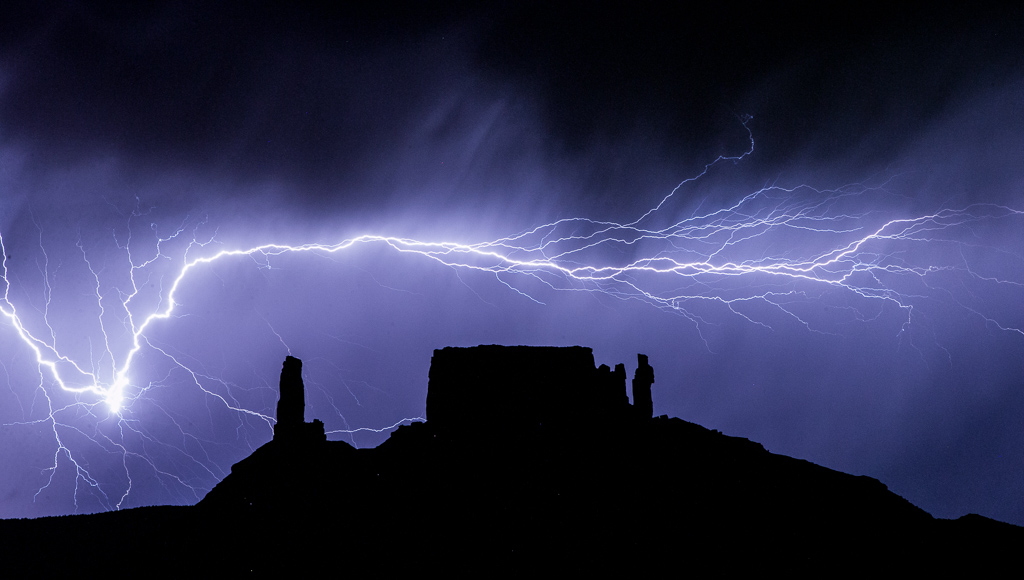 Incredible streak of lightening across the dark sky with the silhouette of rock formations.