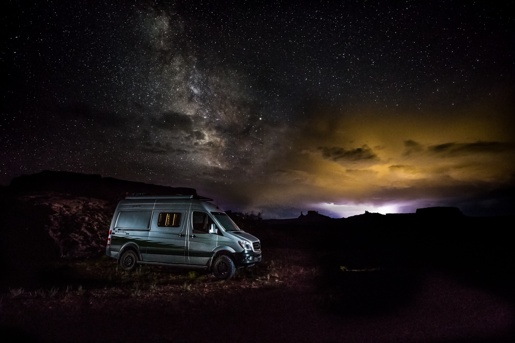 Winnebago Revel parked alone in desert landscape with the Milky Way bright overhead in the nightsky on the left and an approaching storm lighting the sky on the right.