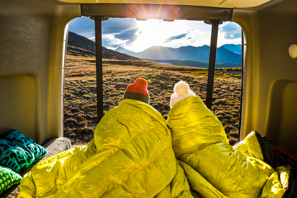 Peter and Kathy huddled in a blanket on the back bed of the Winnebago Revel looking out at the sunset and mountains ahead.