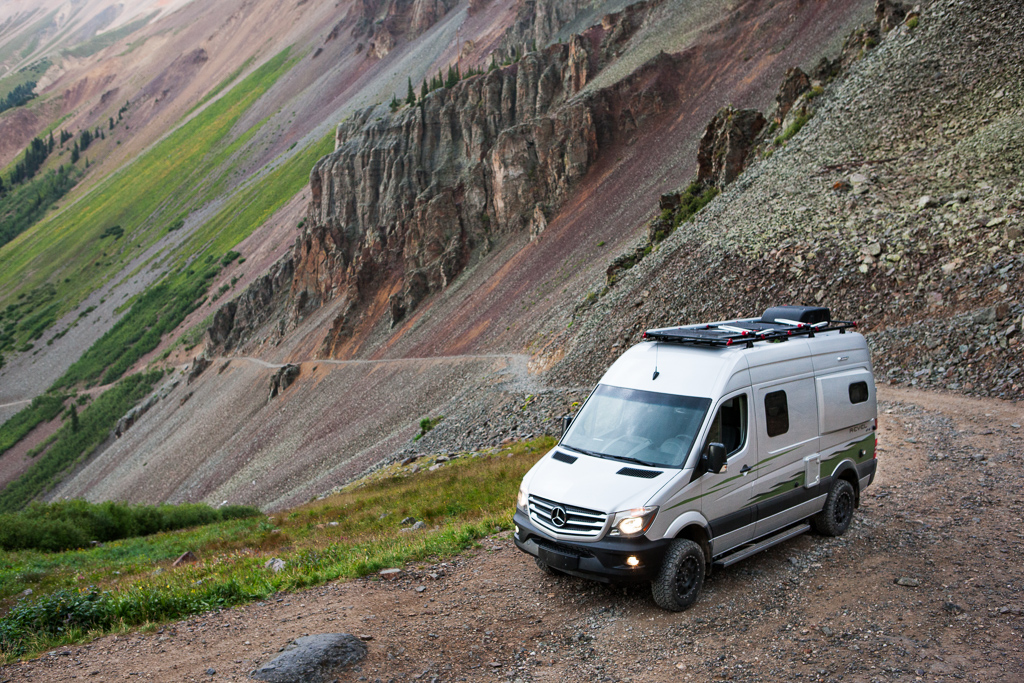 Winnebago Revel parked at the start of an extremely narrow trail along the steep hillside.