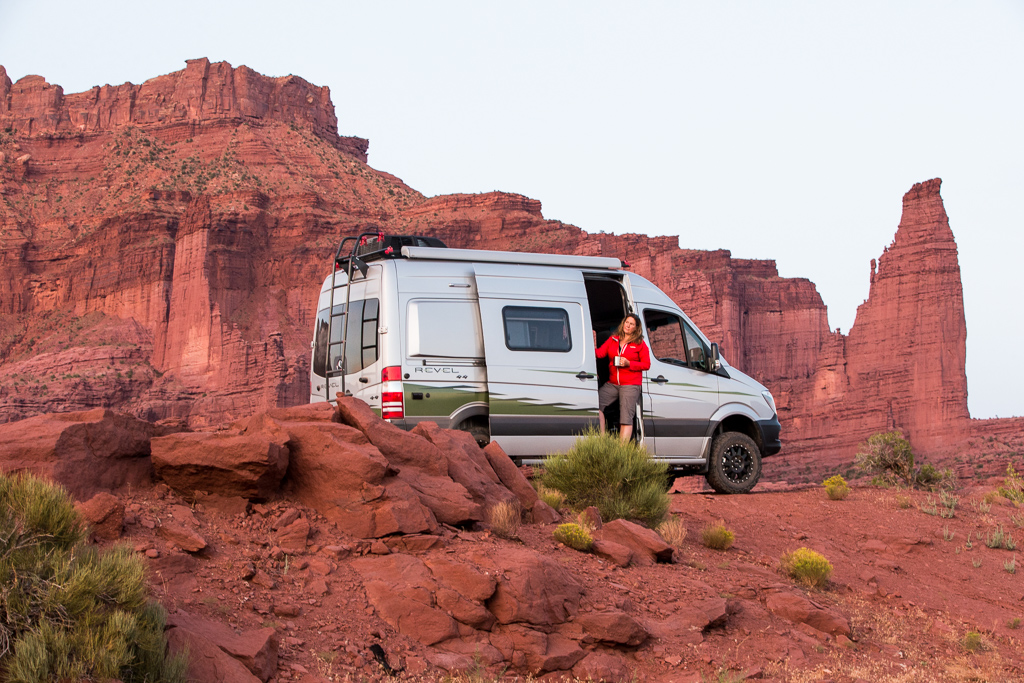 Kathy standing with the side door slightly open on the Winnebago Revel with red rocky canyons in the background.