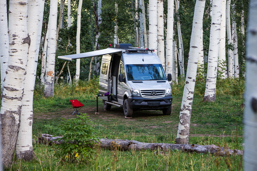 Winnebago Revel parked among trees with awning out.