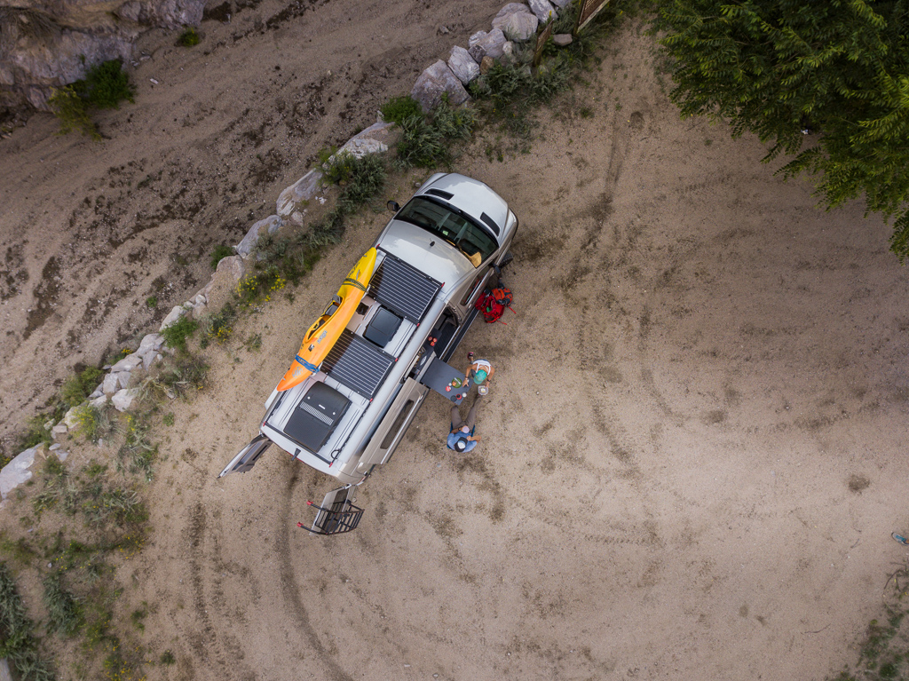 Overhead view of Winnebago Revel with solar panels and a kayak on top parked on dirt ground with Kathy and Peter sitting at the table outside.