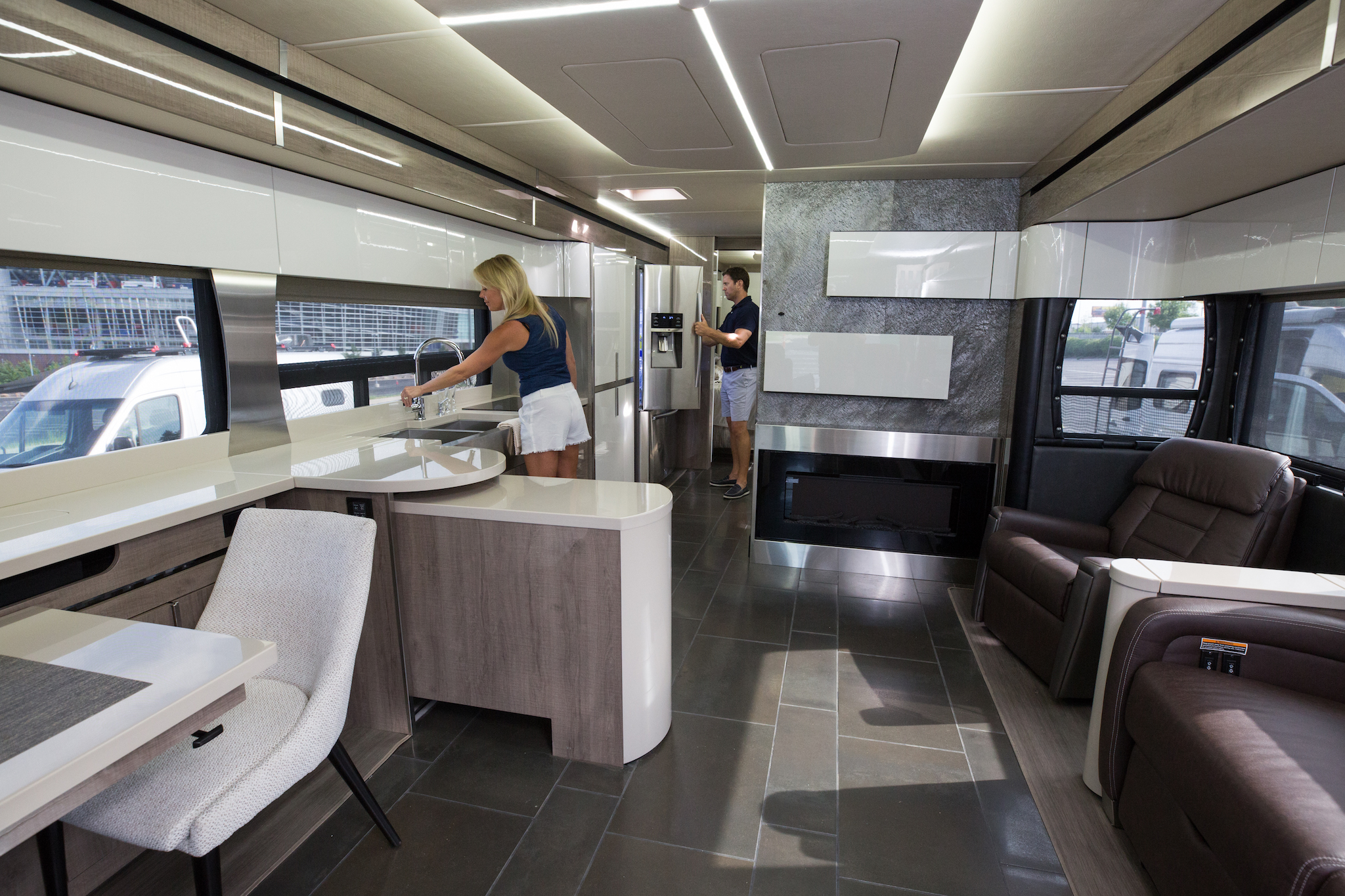 Woman at the kitchen sink and man looking in the fridge of a modern Winnebago Horizon.