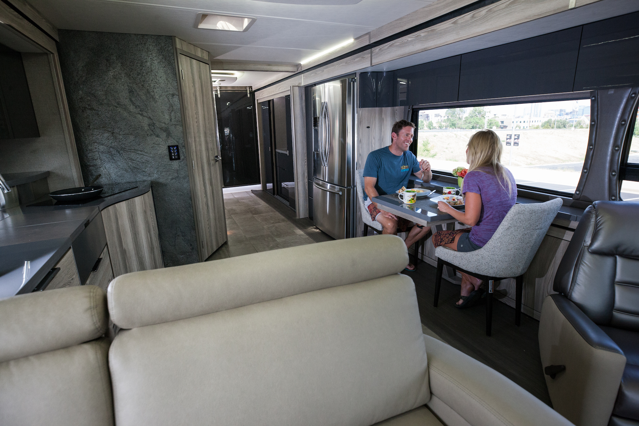 Couple eating at the dinette inside modern looking Winnebago Horizon.