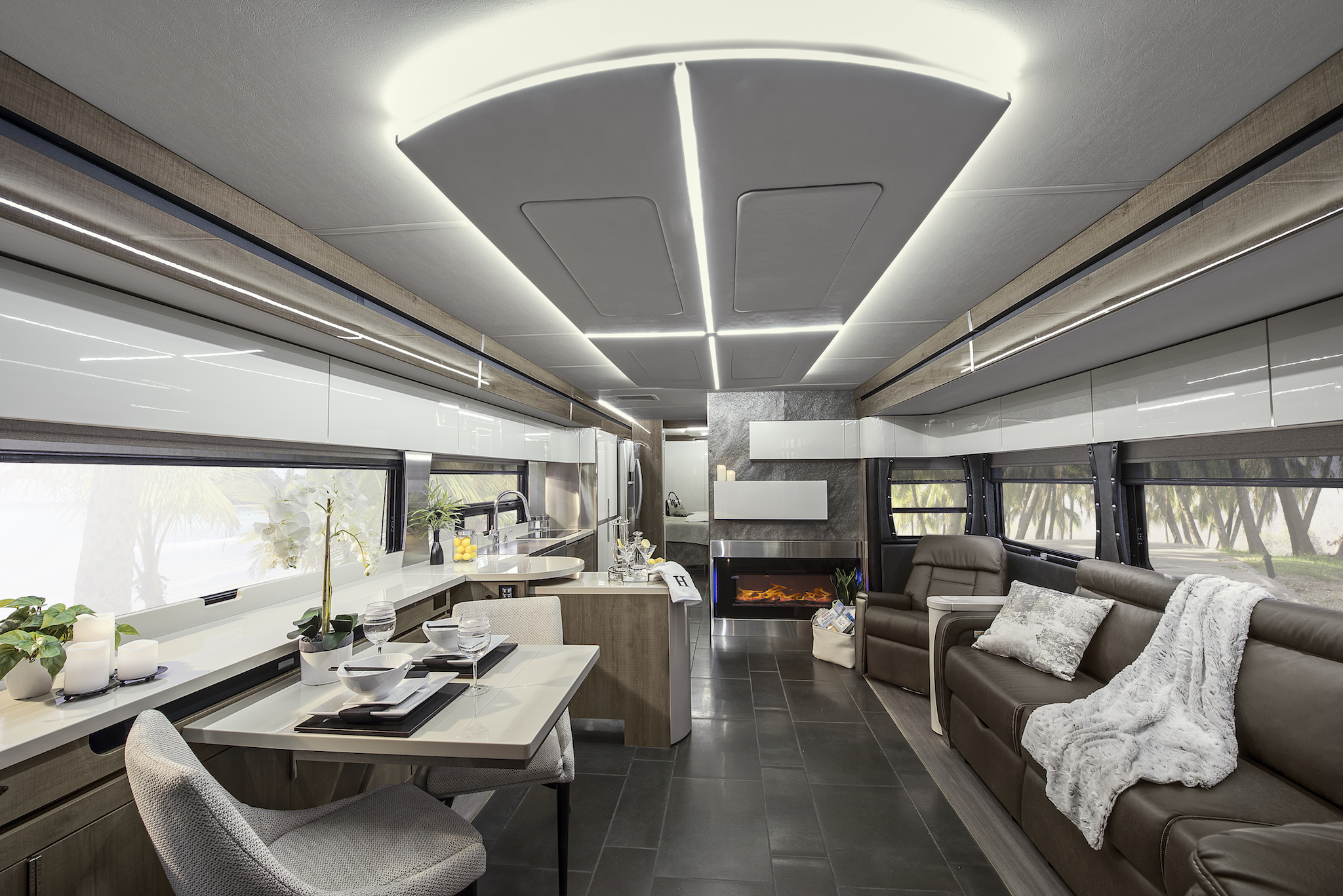 Modern interior of Winnebago Horizon with backlit LED lights on ceiling panel that brighten the space.