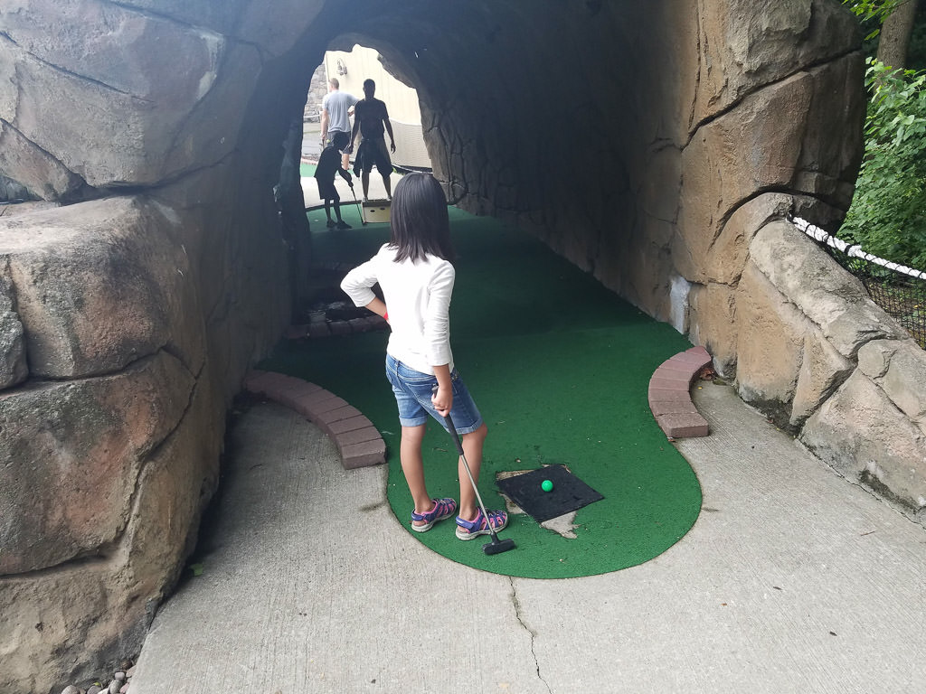 A family playing mini golf