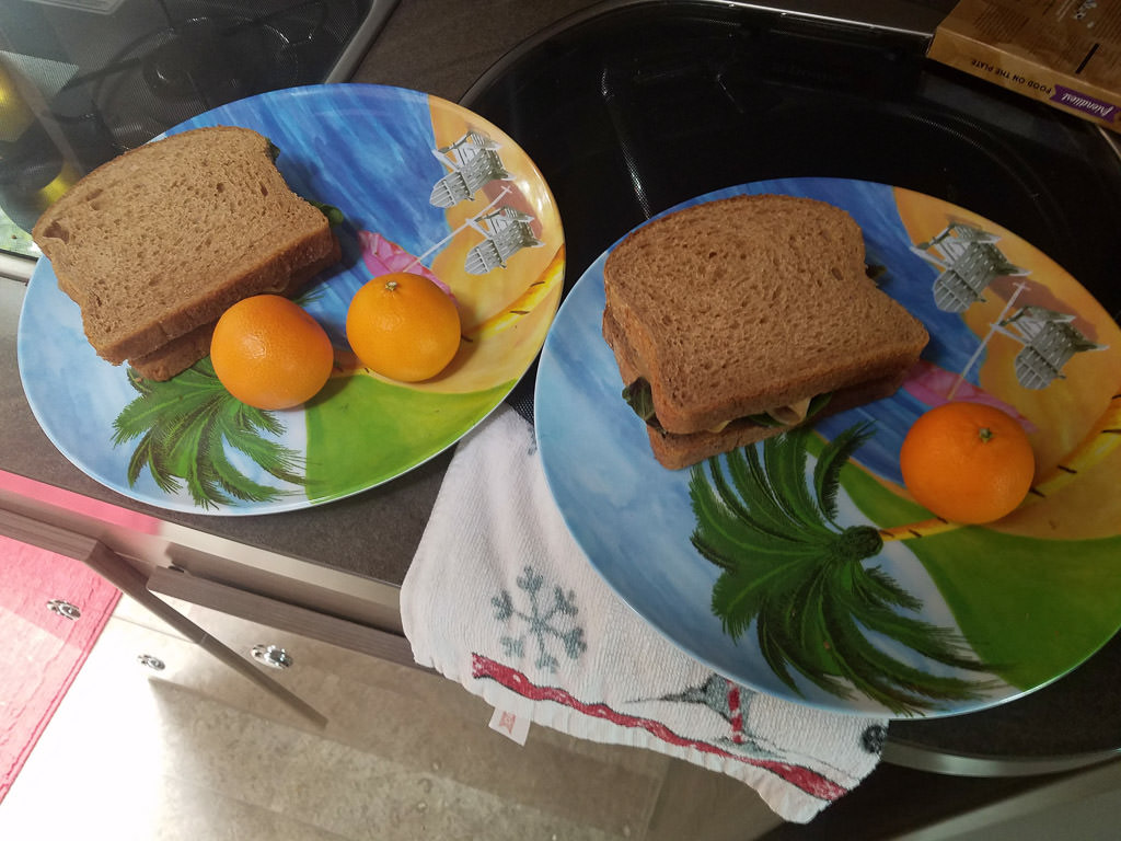Sandwiches and oranges on plates